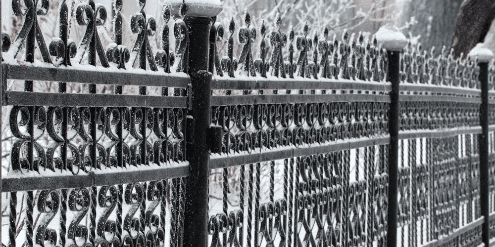 black winter fence with snow